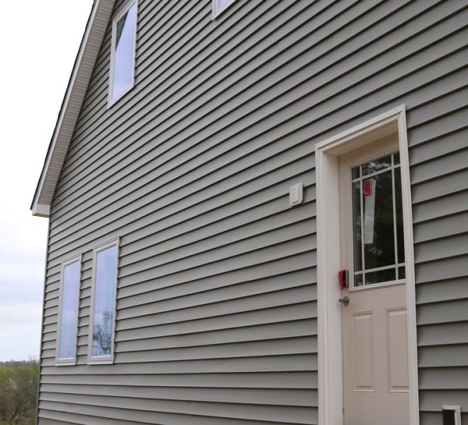 Example of gray siding on large house with cream door