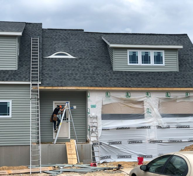 Worker installing new, gray, vinyl siding on home