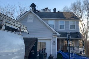 Workers on roof top ripping out old shingles
