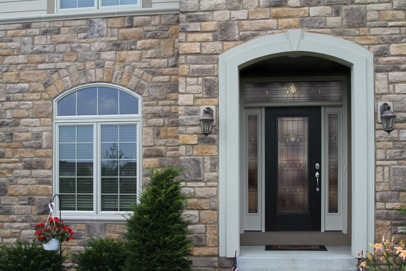 Black Legacy front door with beautiful glass design in stone home