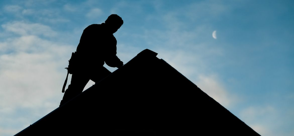 Silhouette of worker at roof peak of fixer upper