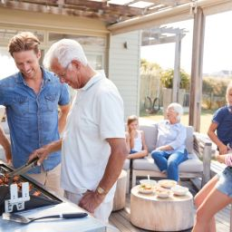Men grilling with family sitting around together