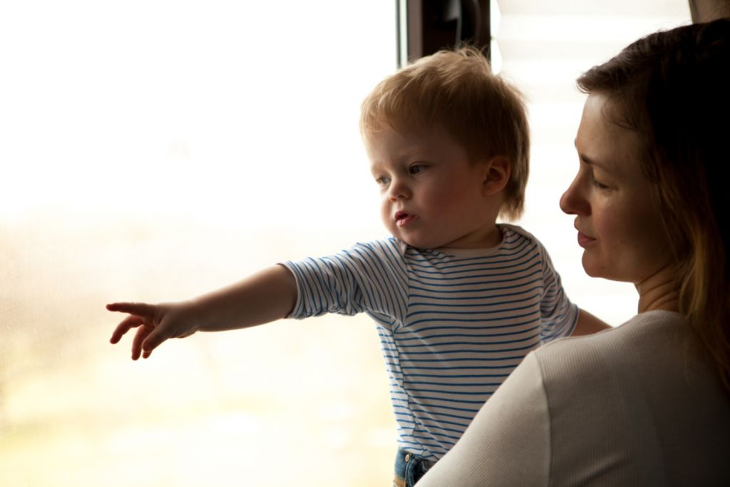 Mom holding baby in front of window