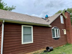 Man on the roof of a house installing new shingles - Trusted Veterans Restoration, Paris VA